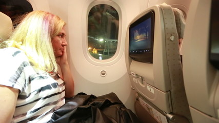 middle age blonde women watching movie in aircraft cabin