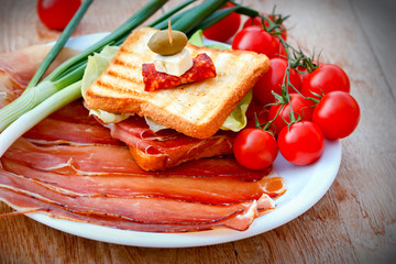 Sandwich with prosciutto, onion and cherry tomatoes