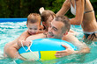 Father and his children having fun in the swimming pool on summe