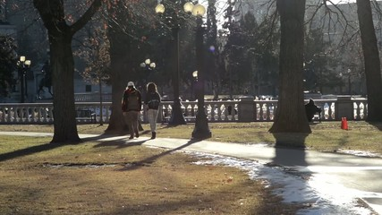 People walking through a city park on a sunny winter afternoon