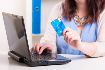 Woman paying by credit card using a computer and the Internet in