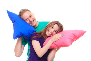 Smiling man and woman holding colorful pillows