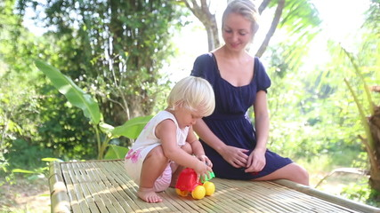 blonde girl dancing and takes small toy car near her mother