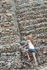 Casual woman, a huge rock wall as background