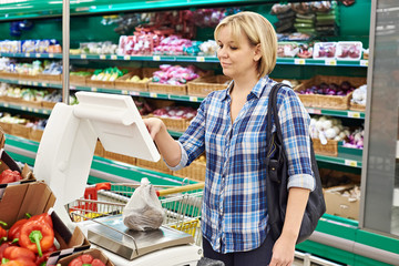 Woman weighing vegetables in supermarket