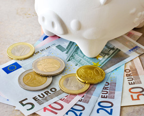 Euro banknotes and coins with piggy bank