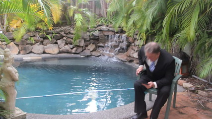 Businessman sitting with tablet by a swimming pool.