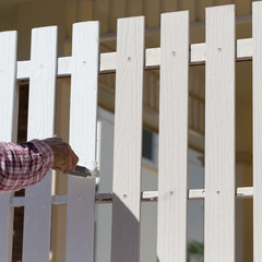 hand worker holding brush painting white on wood fence