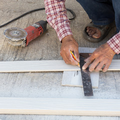 carpenter using ruler to draw a line marking on a wood board