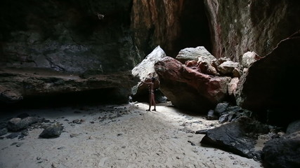 young beautiful brunette girl stand in rocky cave