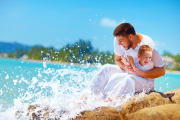 a moment of water splashing on happy father and son