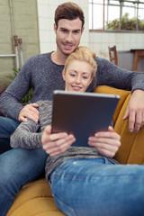 modernes paar schaut zuhause auf tablet-pc