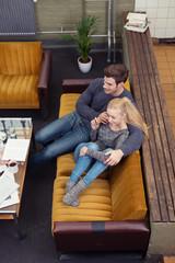 paar sitzt gemütlich auf einem gelben sofa