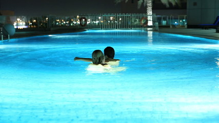 young mother and son playing luxury pool at night