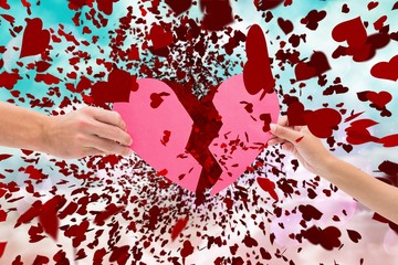 Composite image of hands holding two halves of broken heart