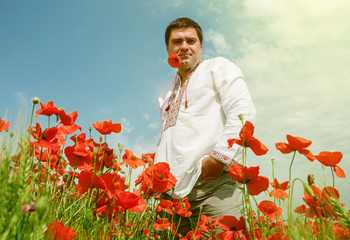 Man in national ukrainian embroidered dress among the poppies fl