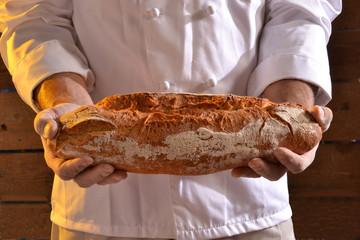 Panadero sujetando pan fresco.