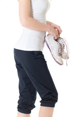 Young woman in sportive outfit with sneaker in her hands