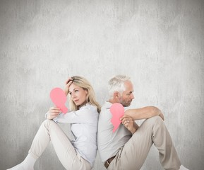 Unhappy couple sitting holding two halves of heart