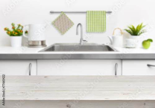 Wooden table on kitchen sink interior background - 77665422