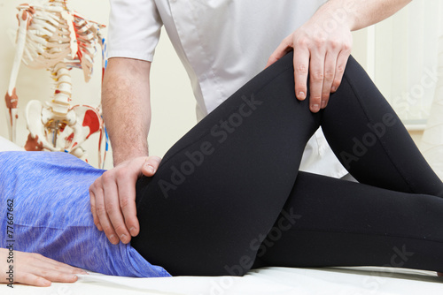 Leinwanddruck Bild Male Osteopath Treating Female Patient With Hip Problem