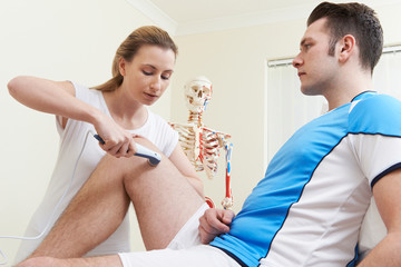 Osteopath Giving Male Client Ultrasound Treatment