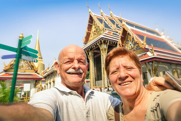 Senior happy couple taking a selfie at Grand Palace temples