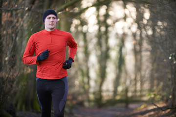 Man On Winter Run Through Woodland