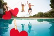 Composite image of cheerful couple jumping into swimming pool - 77669262