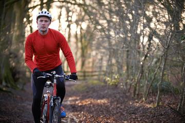 Man Riding Mountain Bike Through Woodlands