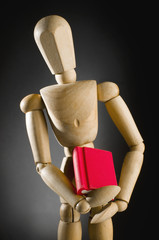 Wooden man holding red book.
