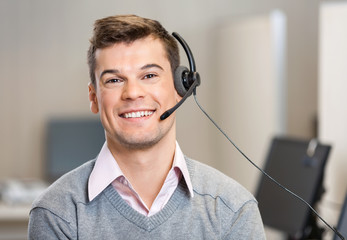 Customer Service Representative Wearing Headset While Smiling In