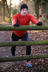 Man Stretching On Run Through Winter Woodland