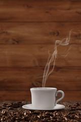 Frischer Kaffee dampft aus Tasse vor Holz
