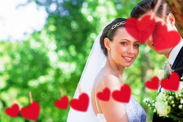 Composite image of loving bride and groom in garden
