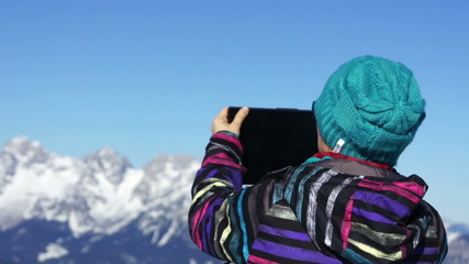 Woman taking photo with digital tablet in the mountains