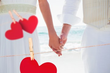Composite image of newlyweds holding hands