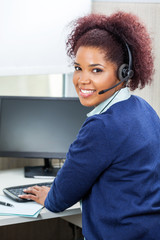 Smiling Customer Service Representative Using Computer