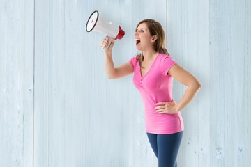Composite image of angry woman with megaphone