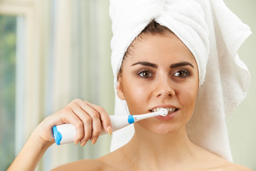 Woman Brushing Teeth With Electric Toothbrush In Bathroom