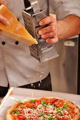 Cocinero preparando pizza,rayando queso parmesano.