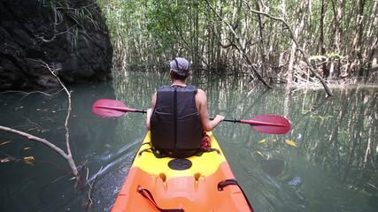 elder man floating in kayak in lagoon past cliff and mangrove