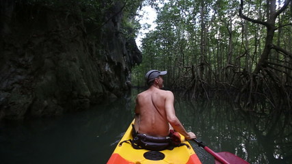 topless elder man rowing in canoe past cliff and mangrove brushw