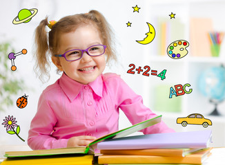 Happy child in glasses reading book. Early education in