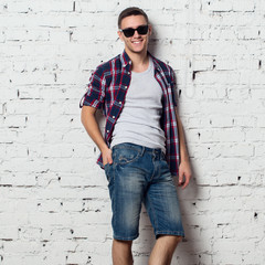 Handsome stylish young man in jeans shorts and shirt. Attractive