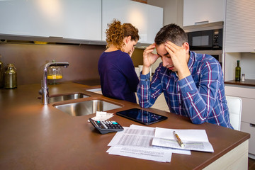 Desperate young couple with debts reviewing their bills