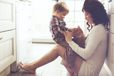 Mother and child playing with cat - 77677401