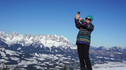Young female taking a self-portrait with her smartphone, Alps