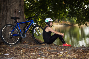 woman relaxing with bike by the lake