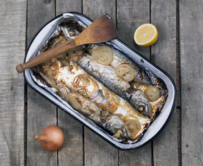 Baked mackerel fish with onion and half lemon on table